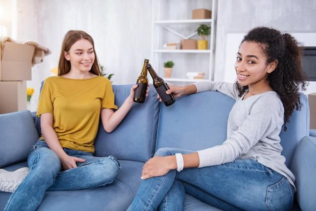 Mini-party. charmante junge mädchen, die auf der couch sitzen und an ihren bierflaschen klirren, während sie den umzug in eine neue wohnung feiern