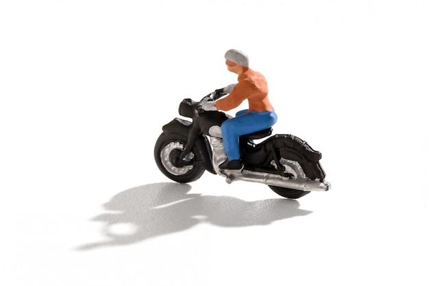 Mini person, die ein motorrad mit schatten reitet