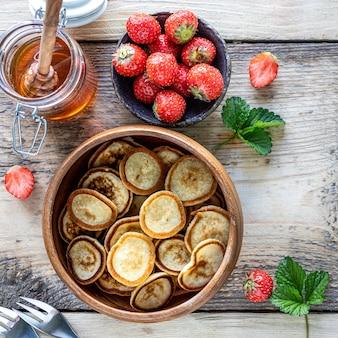 Mini-pfannkuchen in einer holzschale mit erdbeeren und honig