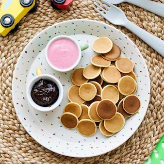 Mini-pfannkuchen kinder-frühstücksleckerbissen mit schokoladenaufstrich und erdbeerjoghurt