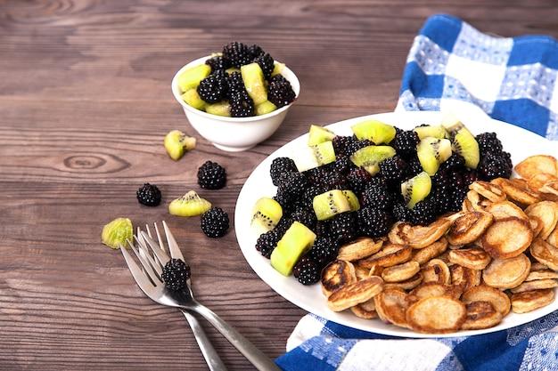 Mini-pfannkuchen mit brombeeren und kiwi-scheiben auf einem teller, zwei gabeln auf einer blauen leinenserviette. dessert.