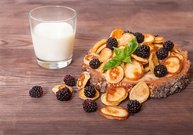 Mini-pfannkuchen mit brombeeren und minzblättern und einem glas milch stehen auf einem holztisch.