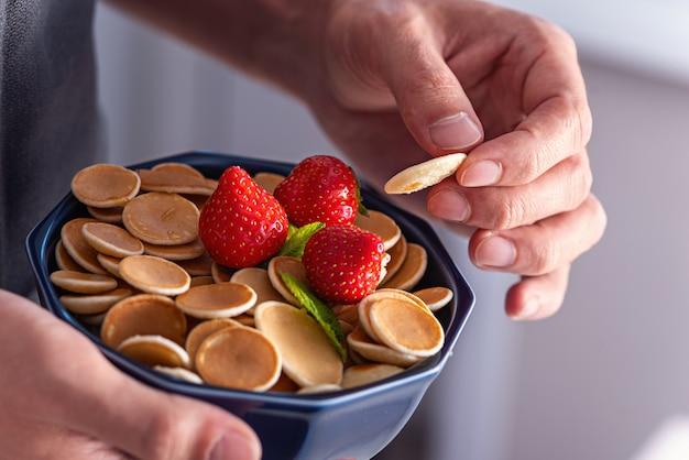 Mini-pfannkuchen-müsli in blauer schüssel mit erdbeeren in den händen der männer, trendiges essen, nahaufnahme