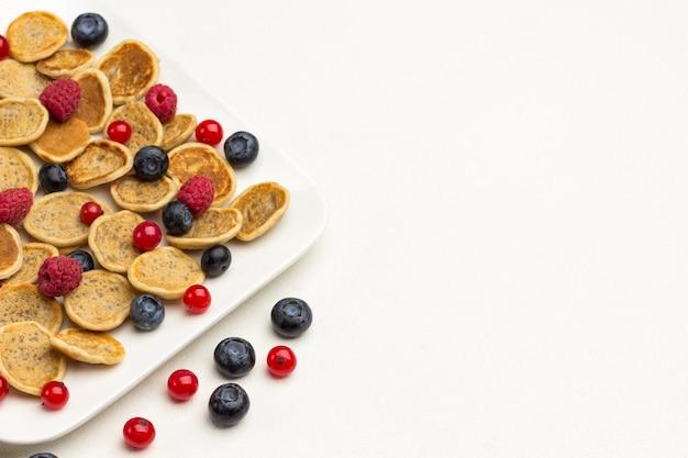 Mini pfannkuchen und beeren in teller. rote johannisbeeren, blaubeeren auf weißem hintergrund. flach liegen. nahansicht. speicherplatz kopieren