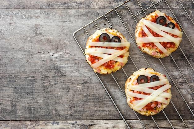 Mini-pizzen der halloween-mumien auf holztisch