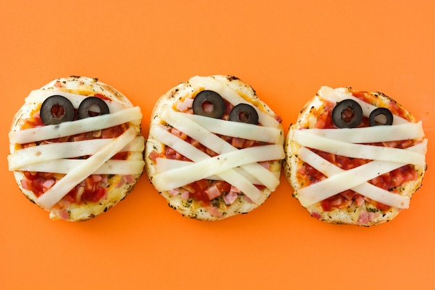 Mini-pizzen der halloween-mumien auf orangefarbenem hintergrund