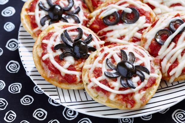 Mini-pizzen mit spinnen und mumien für ein halloween dekoriert