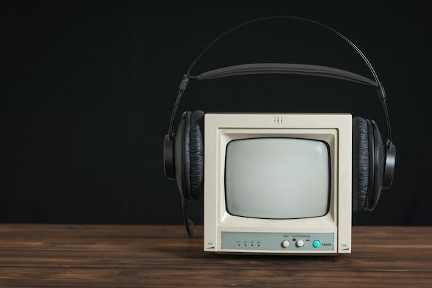 Mini retro-tv mit kopfhörern auf holztisch auf schwarzem hintergrund. technik zur ton- und videowiedergabe.