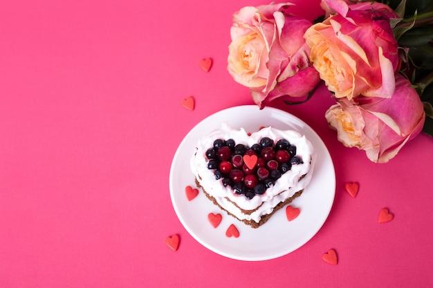 Mini romantischer dessertkuchen zum valentinstag mit rosen. süße kekse mit sahne-belag und rotem herzen für dekor auf rosa. nahaufnahme, kopierraum.