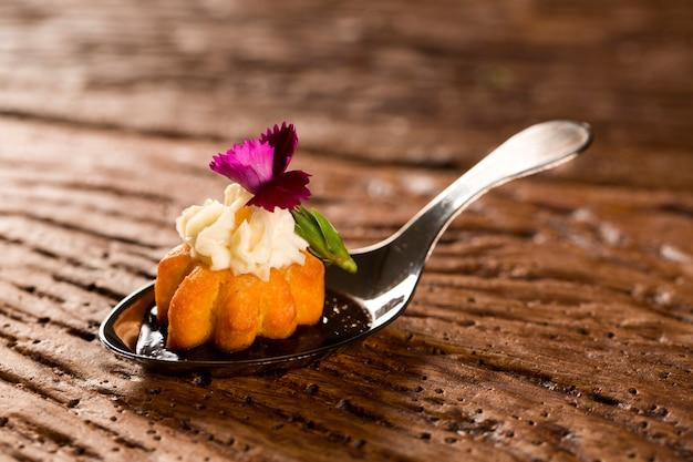 Mini salzige churros, begleitet von aromatisierter kaffeereduktion mit kombu und gefüllt mit frischkäse kandierter orange in einem löffel. probieren sie gastronomisches fingerfood