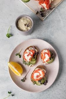 Mini-sandwiches mit räucherlachs, frischkäse, gurke und mikrogrün auf roggenbrot.