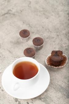 Mini schokoladen brownies und tasse schwarzen tee auf stein.