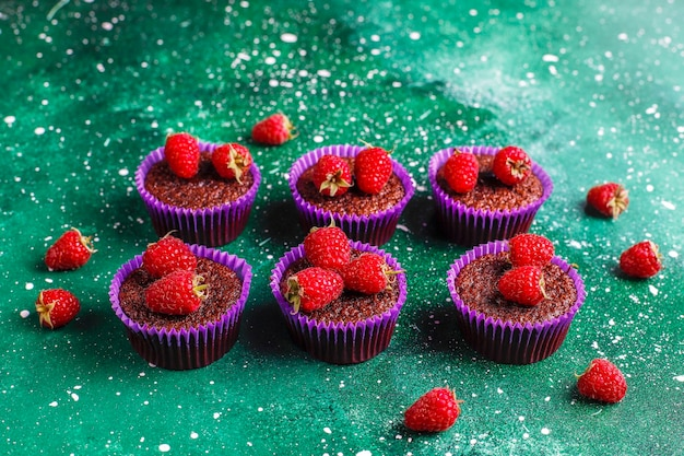 Mini-schokoladen-souffle-cupcakes mit himbeeren.