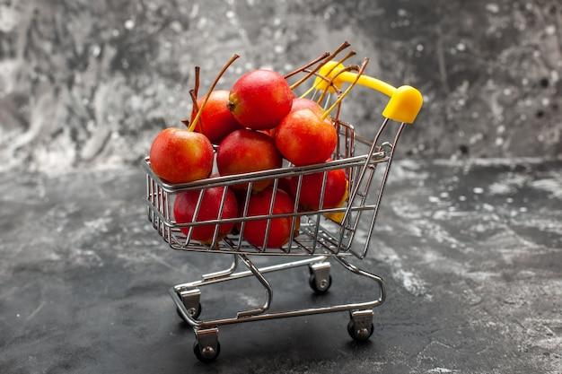 Mini-shopping-chart mit roten kirschen auf grauem hintergrund