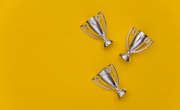 Mini silberne sportmeisterschaftsschalen auf gelbem pastellhintergrund. platz kopieren. sportlicher minimalismus. ansicht von oben