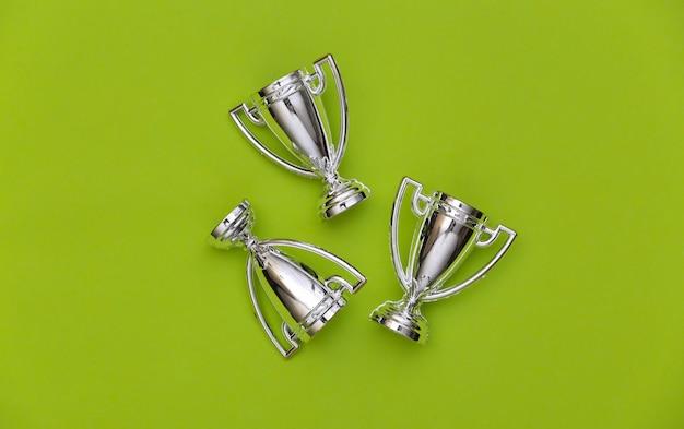 Mini silberne sportmeisterschaftsschalen auf grünem hintergrund. sportlicher minimalismus. ansicht von oben