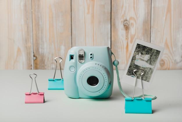 Mini-sofortbildkamera; schnappschuss und büroklammern auf weißem schreibtisch gegen holzwand