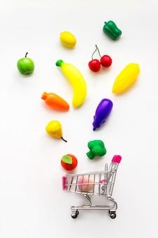 Mini-spielzeuggemüse und -früchte, die in minieinkaufswagen auf weißem hintergrund fallen.