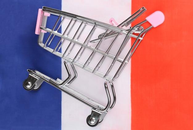 Mini-supermarktwagen auf unscharfem hintergrund der französischen flagge. shopping-konzept.