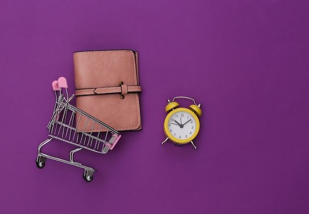 Mini-supermarktwagen mit geldbörse und retro-wecker auf violettem hintergrund. einkaufszeit..