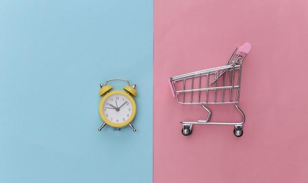 Mini-supermarktwagen und retro-wecker auf rosa blauem pastellhintergrund.