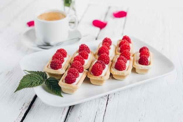 Mini-törtchen mit hüttenkäse und frischen himbeeren und einer tasse kaffee