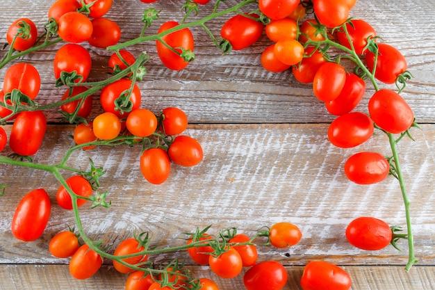 Mini-tomaten auf einem holztisch. flach liegen.