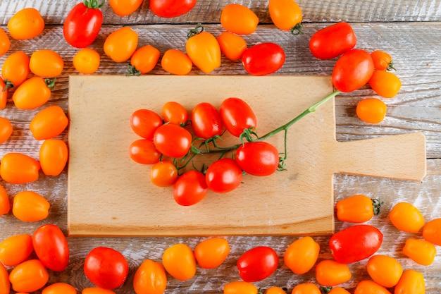 Mini-tomaten auf holz und schneidebrett. flach liegen.