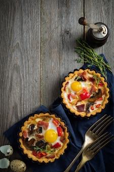 Mini-torte mit gebackenem schinken, pfeffer, pilzen und wachteleiern in cremiger sauce auf einem holzständer
