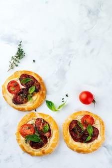 Mini-torten mit getrocknetem fleisch, tomaten, ricotta, thymian, basilikum und oliven auf einem licht