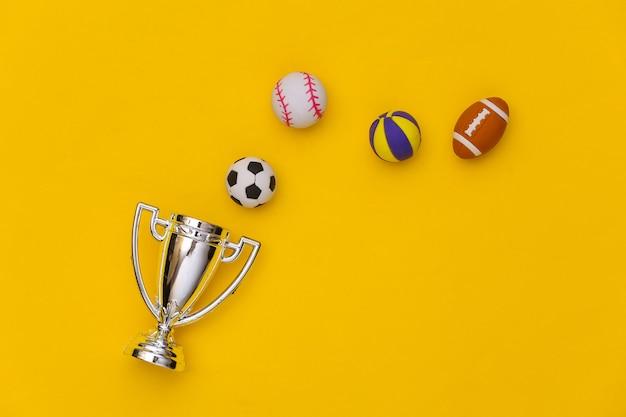 Mini verschiedene sportbälle und meisterpokal auf gelbem hintergrund. minimalismus sportkonzept. ansicht von oben. flach liegen.