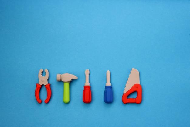 Mini-versionen von schraubenziehern, sägen, hammer und zange für kinder auf blau. Premium Fotos
