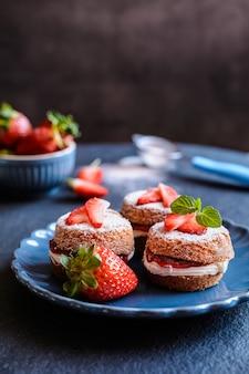 Mini victoria biskuitkuchen mit schlagsahne und erdbeeren