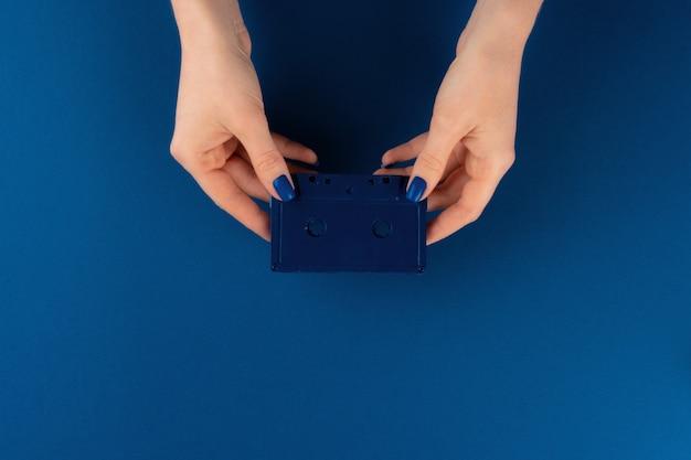 Mini-videokassette in weiblichen händen, draufsicht
