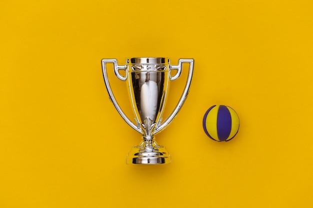 Mini-volleyballball und meisterpokal auf gelbem hintergrund. minimalismus sportkonzept. ansicht von oben. flach legen