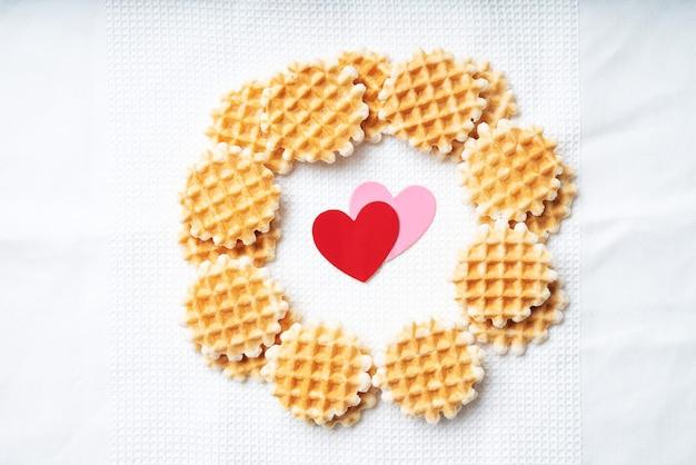 Mini-waffeln mit papierherzen verziert. st valentine konzept. draufsicht. flache lage