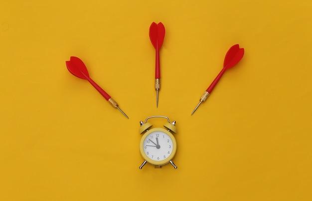 Mini-wecker und darts auf gelbem hintergrund.