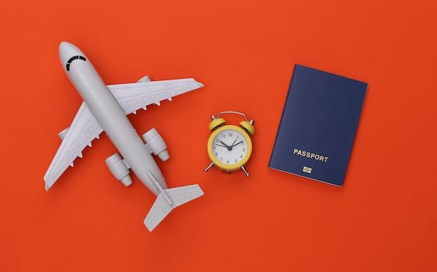 Mini-wecker und flugzeug, reisepass auf orangem hintergrund. zeit zu reisen.