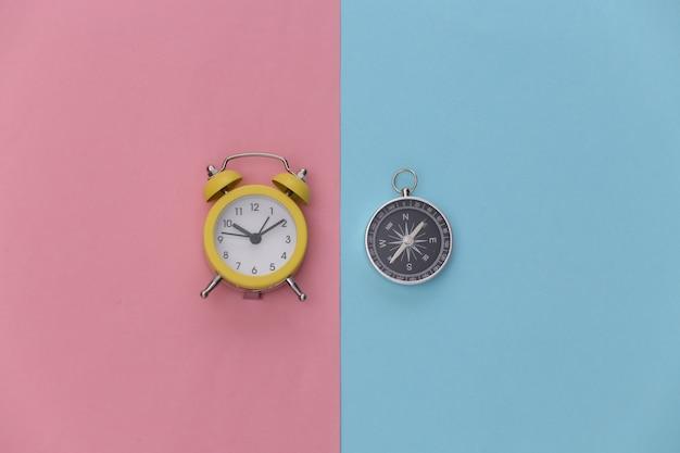 Mini-wecker und kompass auf rosa blauem hintergrund. zeit für abenteuer.