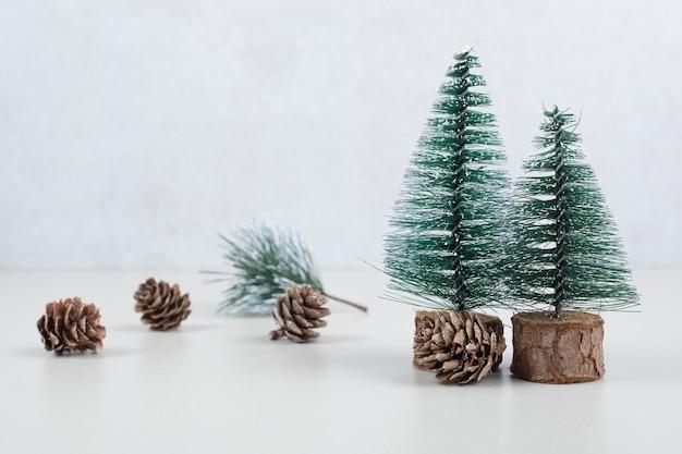 Mini weihnachtsbäume und tannenzapfen auf beiger oberfläche