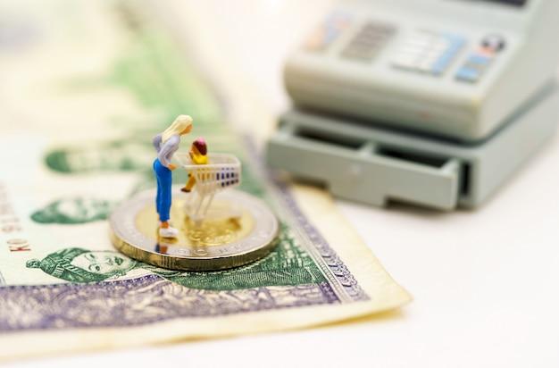 Miniatrue-leute: käufer mit dem warenkorb, der auf münzenstapel steht.