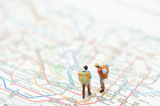 Miniatur 2 menschen stehen auf einer karte der u-bahn-linien in japan.