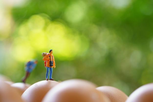 Miniatur 2 personen stehen auf dem gehweg zu beginn der reise um das ziel zu erreichen.