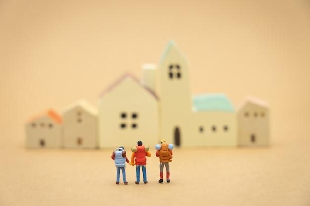 Miniatur 3 personen stehen auf haus- und hotelmodellen, um einen wohnort zu wählen.