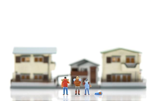Miniatur 3 personen stehen auf haus- und hotelmodellen