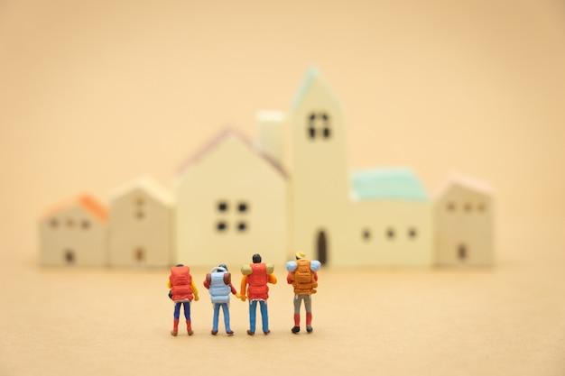 Miniatur 4 personen stehen auf haus- und hotelmodellen, um einen wohnort zu wählen.
