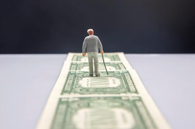 Miniatur-älterer mann geht über dollarnoten weg
