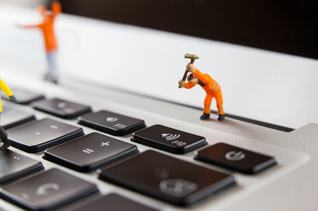 Miniatur-arbeiter, die ein laptop-tastatur reparieren