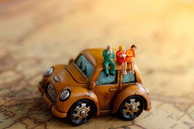 Miniatur der leute, die auf dem weinleseauto und der karte mit trinkendem kaffee sitzen