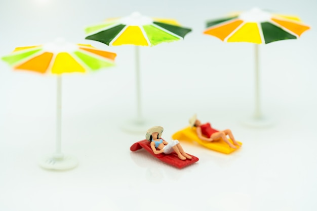 Miniatur der touristen, die auf dem strand ein sonnenbad nehmen